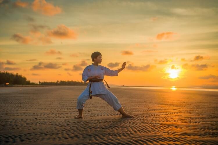 Woman practicing karate on beach with sunset